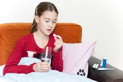 Krankes Mädchen, das im Bett einnimmt Medizinpillen mit Wasserglas liegt Stockfoto