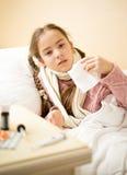 Krankes Mädchen, das im Bett liegt und Papiergewebe hält Stockbild