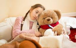 Krankes Mädchen, das im Bett mit braunem Teddybären stillsteht Stockfotos