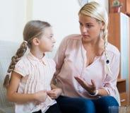 Krankes Mädchen mit den Schmerz im Magen und in besorgter Mutter zuhause Lizenzfreies Stockbild