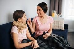 Krankes Mädchen sitzen zusammen mit ihrer Mutter Sie hält Mund geöffnet und erhält Löffel mit Sirup Griffflasche der jungen Frau  lizenzfreies stockbild