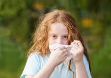 Krankes Niesen des kleinen Mädchens im Taschentuch lizenzfreies stockbild