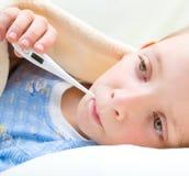 Krankes und trauriges Kind im Bett Stockbild