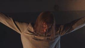 Krankzinnige die mens met dwangbuiskokers aan plafond in de verlaten bouw worden gebonden stock video