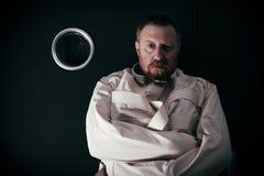 Krankzinnige mens in een cel die een dwangbuis dragen Stock Foto's