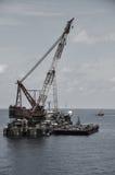 Kranpråm som lyfter tung last eller den tunga elevatorn i frånlands- fossila bränslenbransch Stort fartyg som arbetar för att led royaltyfri foto