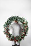 Krans för hållande jul för ung kvinna stor i händer i ljus, säsongsbetonade ferier, lantligt tema som smyckar royaltyfri bild
