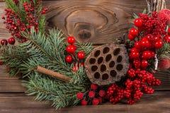 Krans med lotusblommablomman och röda bär Julvinterram på mörk träbakgrund röda element royaltyfria foton