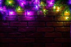 Krans och girlander av kulöra ljusa kulor Julbakgrund med ljus och utrymme för fri text Gräns för julljus Royaltyfri Foto