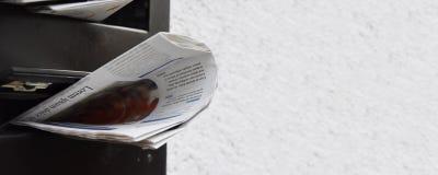 Kranten in een brievenbus stock fotografie