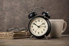Kranten, glazen, wekker en koffiekop op Desktop royalty-vrije stock afbeeldingen