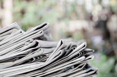 Kranten op de lijst met openluchttuin of groene achtergrond worden en worden gestapeld gevouwen die Close-upkrant en selectief na royalty-vrije stock fotografie