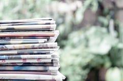 Kranten op de lijst met openluchttuin of groene achtergrond worden en worden gestapeld gevouwen die Close-upkrant en selectief na stock afbeelding