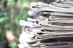 Kranten op de lijst met openluchttuin of groene achtergrond worden en worden gestapeld gevouwen die Close-upkrant en selectief na stock fotografie