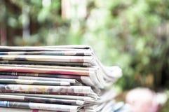 Kranten op de lijst met tuin of groene achtergrond worden en worden gestapeld gevouwen die Close-upkrant en selectief nadrukbeeld royalty-vrije stock afbeelding