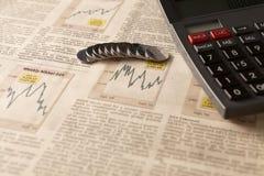 Kranteneffectenbeurs met calculator en geld Stock Afbeeldingen
