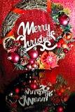 Kranz mit Weihnachtsdekorationen und -text: Frohe Weihnachten Stockfotos
