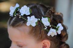 Kranz von künstlichen Blumen im Haar eines kleinen Mädchens, acces Stockfotografie