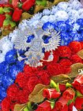 Kranz von künstlichen Rosen in der Trikolore und Emblem des russischen Wappens in der Form des doppelköpfigen Adlers Lizenzfreies Stockfoto