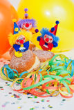 Krapfen or Donuts with clowns and streamer. Donuts with clowns and streamer in front of yellow and orange balloons on children's birthday Royalty Free Stock Photo