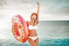 Krasnodar Gegend, Katya Genießen der Sonnenbräunefrau im weißen Bikini mit Donutmatratze nahe dem Ozean stockfoto