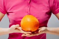 Krasnodar Gegend, Katya PampelmusenZitrusfrucht mit Trinkhalm in der weiblichen Hand auf Grau Gesunde Nahrung und Getränk lizenzfreie stockfotografie