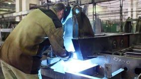 Krasnodar, Rússia - 01 25 2018: O soldador funciona a serra circular, corta o metal Moscas da faísca do metal quente no movimento vídeos de arquivo