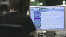 KRASNODAR, RUSIA, EL 13 DE ENERO DE 2013: Ingeniero de sonido que trabaja en el ordenador almacen de metraje de vídeo