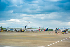 KRASNODAR, RUSSIA - APRIL 19, 2017: Aircraft of different airlines at the airport. Storm clouds in the sky. Copy space. Royalty Free Stock Photography