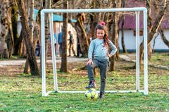 Young Caucasian goalkeeper girl with flushed face posing by outdoor football goal with foot put on ball looking into camera royalty free stock photography