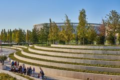 Krasnodar, Russia - October 7, 2018: Schoolchildren with bicycles on the background of smooth lines of terraces in the park Krasno royalty free stock image