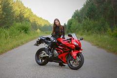 KRASNOJARSK, RUSSIA - 28 giugno 2018: Bello motociclista della ragazza in ingranaggio pieno e casco su Honda rosso e nero 2005 CB fotografia stock