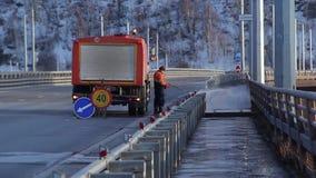 Krasnojarsk, Russia - 25 marzo 2017: Strada di pulizia del lavoratore di manutenzione della via con la corrente ad alta pressione archivi video