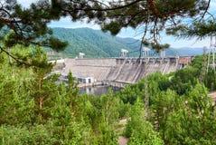 Krasnoyarsk Dam is powerful Siberian hydroelectric power. Dam is powerful Siberian hydroelectric power plant through green branches of forest. Krasnoyarsk stock photo