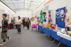 Women walk and look at handmade goods in a large pavilion of the exhibition hall at the traditional traditional city fair. KRASNOYARSK, Krasnoyarsk Region/ RF stock photos