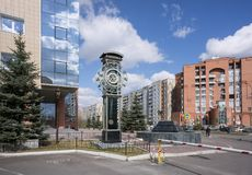 A beautiful sculpture of a clock with signs of constellations, against a background of a city landscape. KRASNOYARSK, RF - April 25, 2015: A beautiful sculpture stock photography