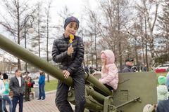 The boy is sitting on the antiaircraft artillery gun, which stand near the museum of the Victory Memorial during the celebration. KRASNOYARSK, RF - May 9, 2018 stock photos