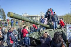 Children play on the tank on the central square of Krasnoyarsk among the exhibition of artillery big guns, during the celebration. KRASNOYARSK, RF - May 9, 2013 royalty free stock photo