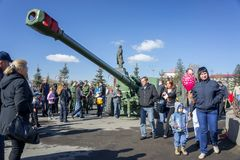 People are walking on the central square of Krasnoyarsk among the exhibition of artillery big guns, during the celebration. KRASNOYARSK, RF - May 9, 2013 royalty free stock photos