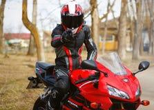 KRASNOYARSK ROSJA, Kwiecień, - 21, 2018: Piękny motocyklista w pełnej przekładni i hełm na czerwieni Honda czerni i 2005 CBR 600  Obrazy Royalty Free