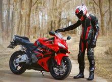 KRASNOYARSK ROSJA, Kwiecień, - 21, 2018: Piękny motocyklista w pełnej przekładni i hełm na czerwieni Honda czerni i 2005 CBR 600  Fotografia Royalty Free
