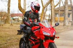 KRASNOYARSK ROSJA, Kwiecień, - 21, 2018: Piękny motocyklista w pełnej przekładni i hełm na czerwieni Honda czerni i 2005 CBR 600  Obraz Royalty Free