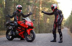 KRASNOYARSK, RUSSIA - April 23, 2019: Beautiful motorcyclist in full gear and helmet on a red and black Honda 2005 CBR 600 RR stock photo