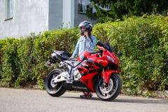 KRASNOYARSK, RUSSIA - AUGUST 09, 2017: A Girl motorcyclist wearing a helmet and red sport bike Honda CBR 600 RR PC37 2005.  royalty free stock photos