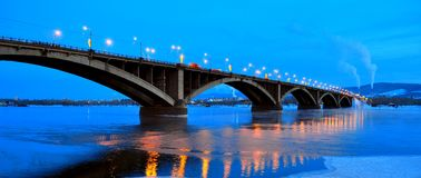 Krasnoyarsk Russia - January 2017 evening view of the Communal bridge across the Yenisei River with reflection in the water the bu. Rning lanterns Stock Photo