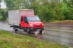 Iveco Daily. Krasnoyarsk, Russia - July 30, 2018: Iveco Daily red color passing on the wet road to a rain royalty free stock photo