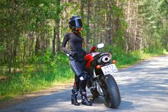 KRASNOYARSK, RUSSIA - June 23, 2018: Beautiful girl motorcyclist in full gear and helmet on a red and black Honda 2005 CBR 600 RR Royalty Free Stock Photos