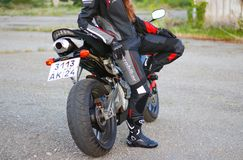 KRASNOYARSK, RUSSIA - June 23, 2018: Beautiful girl motorcyclist in full gear and helmet on a red and black Honda 2005 CBR 600 RR Stock Photos