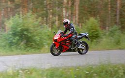 KRASNOYARSK, RUSSIA - June 28, 2018: Beautiful motorcyclist in full gear and helmet on a red and black Honda 2005 CBR 600 RR Royalty Free Stock Photography