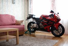 KRASNOYARSK, RUSSIA - March 6, 2019: Red and black sportbike Honda CBR 600 RR 2005 PC37 in house. The motorcycle in the apartment. Winter storage stock images